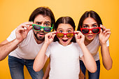 Portrait of nice lovely attractive cheerful amazed people having fun day wearing colorful modern eyewear omg gesture isolated over shine vivid pastel yellow background.