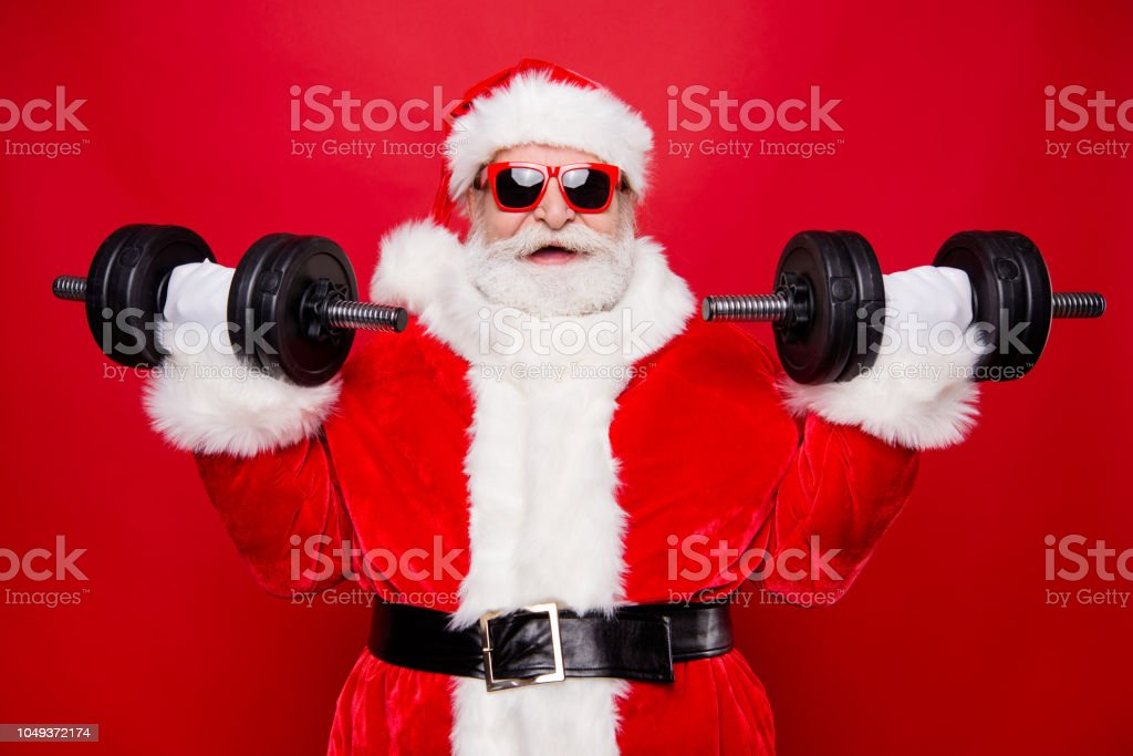 Portrait of nice optimistic positive modern stylish strong sporty muscular virile Saint Nicholas in gloves fur white red winter clothes holding lifting two big dumbbells isolated over red background royalty-free stock photo