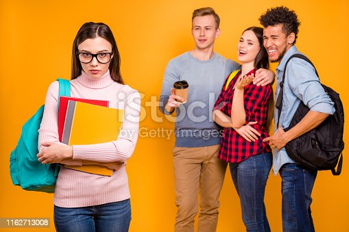 1092709104istockphoto Portrait of nice-looking attractive lovely cheerful cheery company discussing gossiping about expelled odd unwanted intellectual girl isolated over bright vivid shine yellow background 1162713008