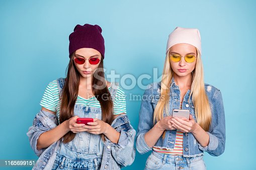 istock Portrait of nice-looking attractive lovely focused girls browsing internet online wi-fi connection isolated over bright vivid shine blue green turquoise background 1165699151