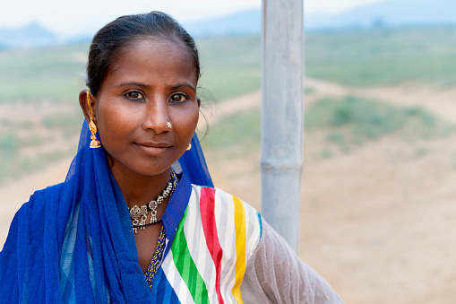 Pushkar, India - November 06, 2019: Portrait of nomadic Kalbeliya gypsy woman with beautiful black hair in colorful Indian clothes in Thar desert on November 06, 2019 near Pushkar, Rajasthan, India.