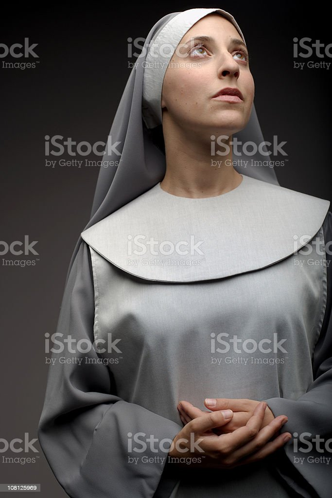 Portrait of Nun With Folded Hands and Looking Away stock photo