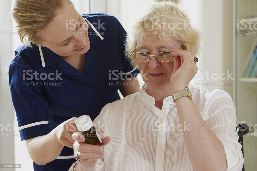 portrait of nurse helping senior woman with medication royalty-free stock photo
