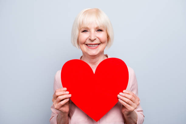 portrait of old adult blonde caucasian glad lady holding hands big red paper heart shape, smiling over grey background, isolated - senior valentine stock photos and pictures