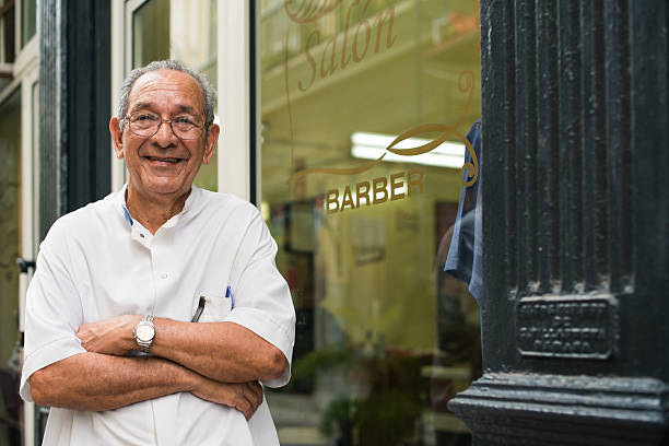 portrait of old barber smiling in hair salon senior hispanic barber in old fashion barber's shop, posing and looking at camera with arms crossed near shop window spanish and portuguese ethnicity stock pictures, royalty-free photos & images
