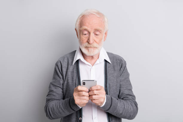 Portrait of old white hair serious man type telephone wear dark sweater isolated on grey background stock photo