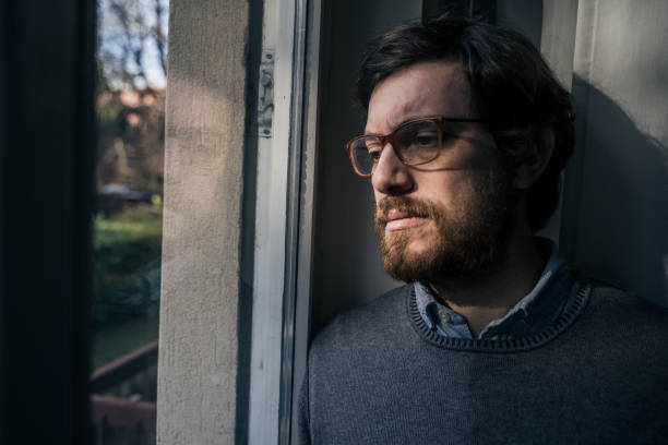 Portrait of one guy longing and looking through window stock photo