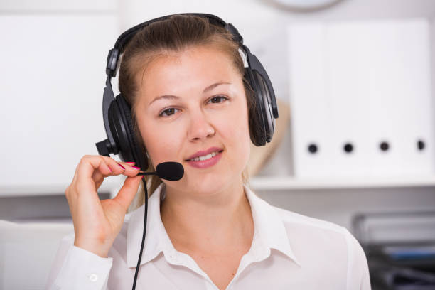 Portrait of operator female which is talking with client stock photo