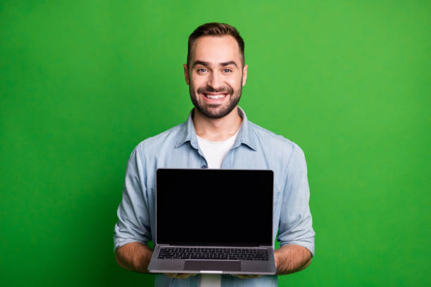 Portrait of optimistic funky guy show laptop wear blue shirt isolated on vibrant green color background stock photo