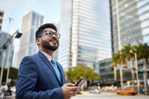 Portrait of Optimistic Hispanic Businessman with Smart Phone stock photo