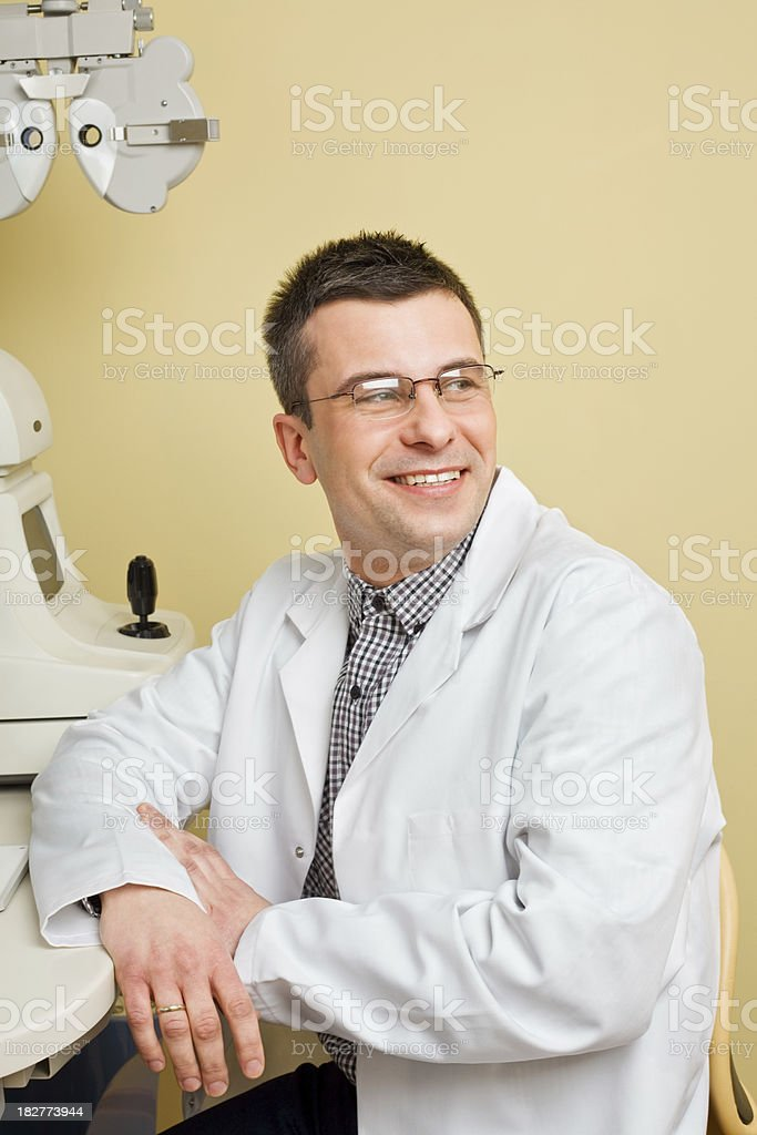 Portrait Of Optometrist In His Office Portrait of a young optometrist looking away and smiling. 30-34 Years Stock Photo