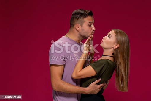 istock Portrait of outraged displeased woman gesturing to stop with hand while man trying to kiss her on burgundy background 1133585253