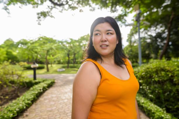 retrato de mulher asiática com sobrepeso vestindo amarelo alaranjado vestido relaxante no parque a bangkok tailândia - body positive - fotografias e filmes do acervo