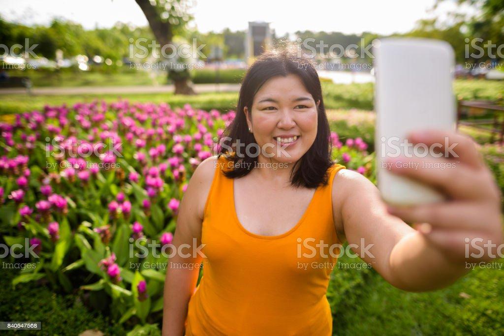 超重的亞洲女人穿著黃色橙色畫像穿在泰國曼谷公園放鬆圖像檔