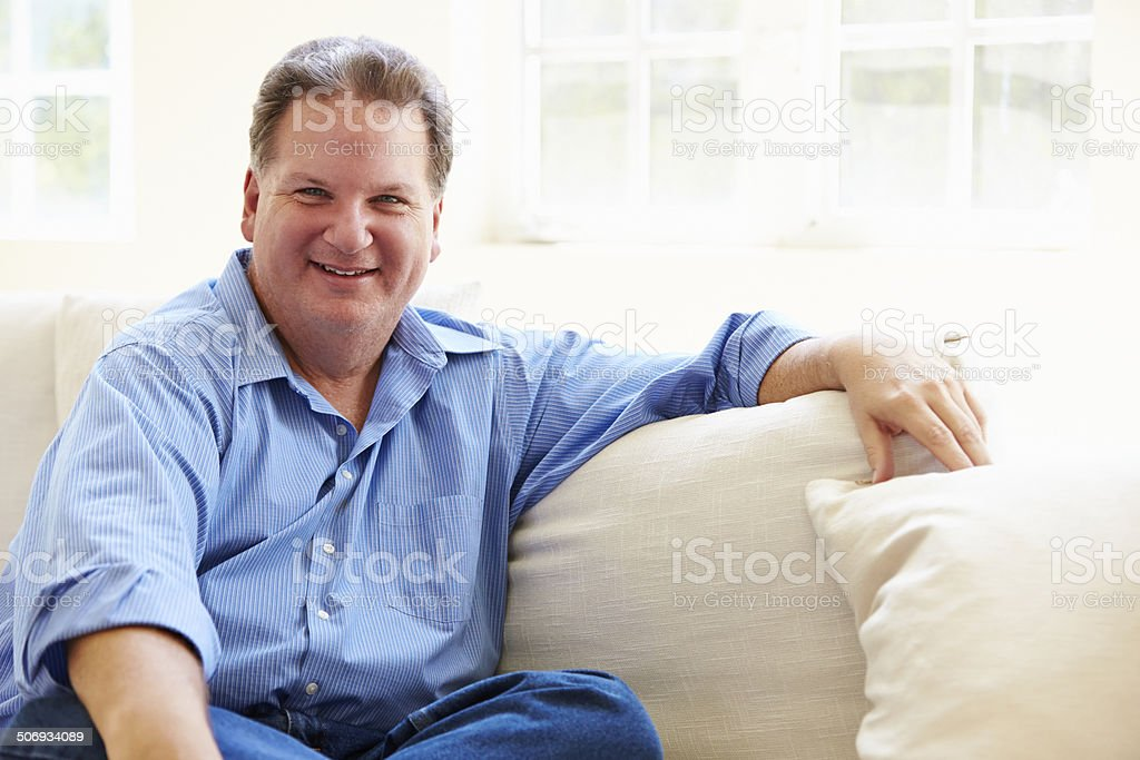 Portrait Of Overweight Man Sitting On Sofa stock photo