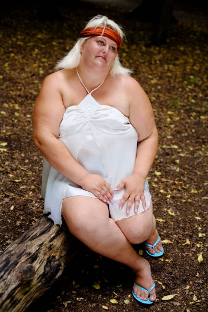 Portrait of Overweight Woman Sitting on Log in Forest stock photo