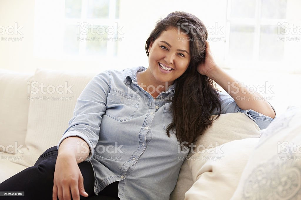 Portrait Of Overweight Woman Sitting On Sofa stock photo