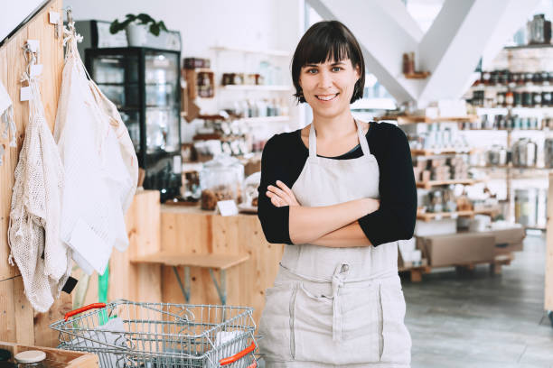 Portrait of owner of sustainable small local business. Female seller assistant of zero waste shop on interior background of shop. stock photo