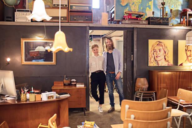 portrait of owners standing in furniture store - malerei türen stock-fotos und bilder