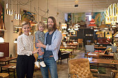 Portrait of happy owners with son at furniture store. Smiling family is standing together at decor shop. They are wearing casuals.