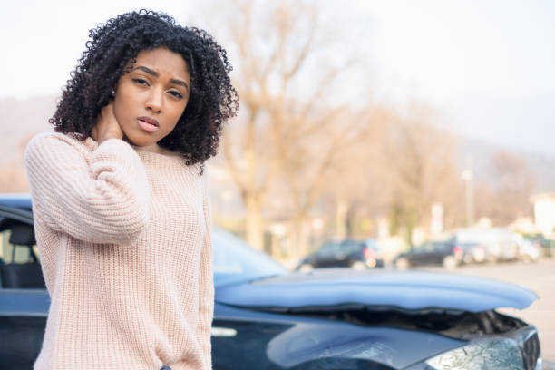 Portrait of painful young black woman after car crash stock photo