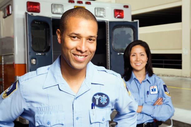 Portrait of paramedics in front of ambulance Portrait of paramedics in front of ambulance civil servant stock pictures, royalty-free photos & images