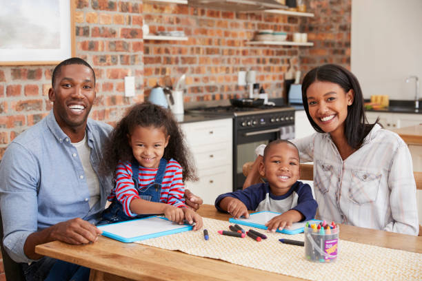 Portrait Of Parents And Children Drawing At Table stock photo