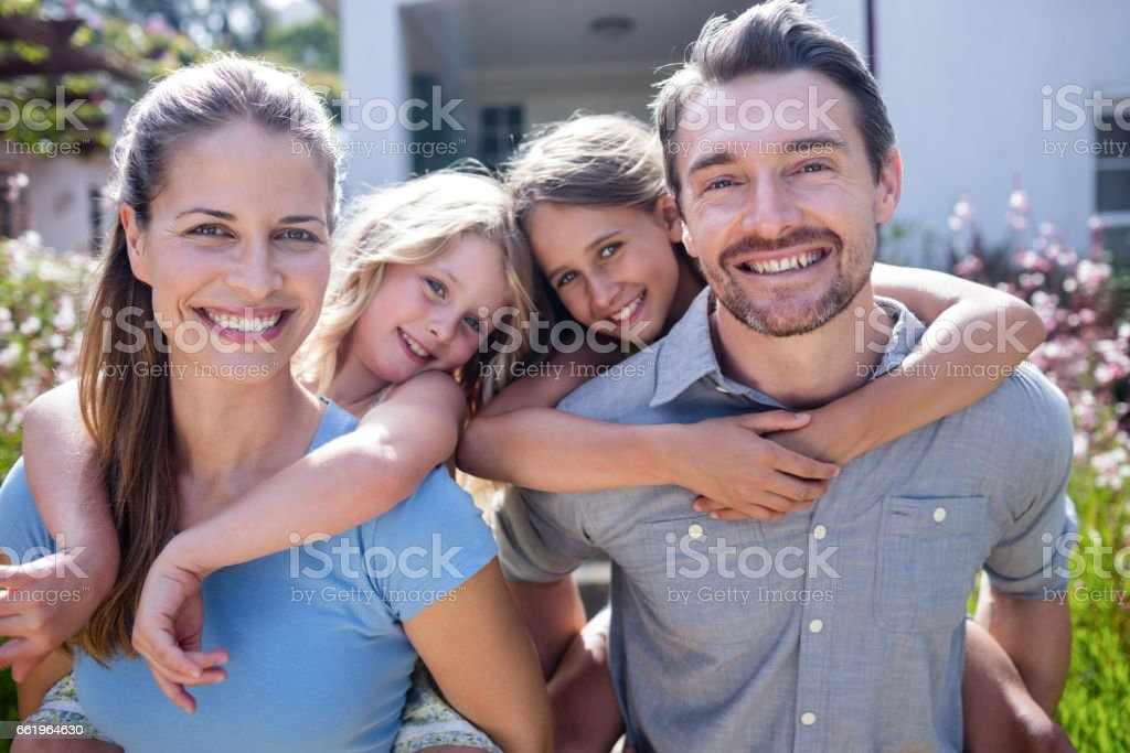 Portrait of parents giving a piggy back to daughters royalty-free stock photo