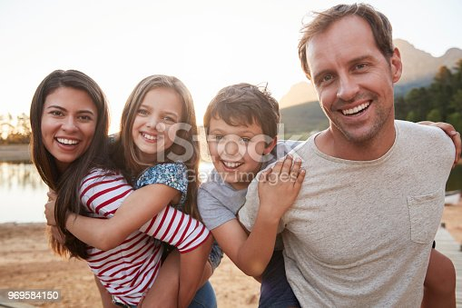 Portrait Of Parents Giving Children Piggyback Ride In Countryside