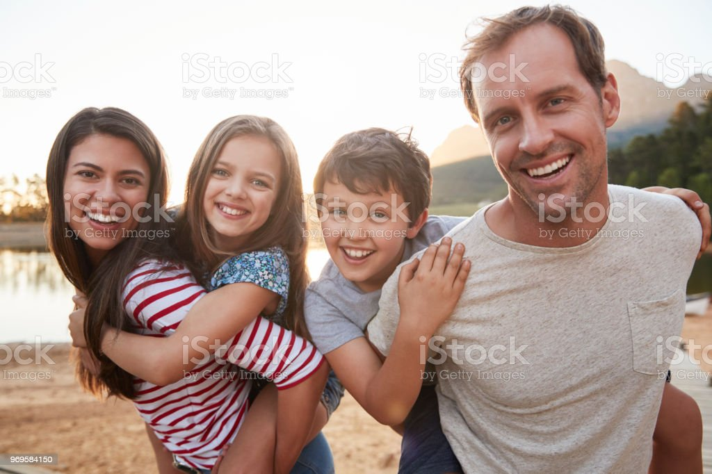 Portrait des Parents donnant enfants Piggyback Ride dans campagne - Photo