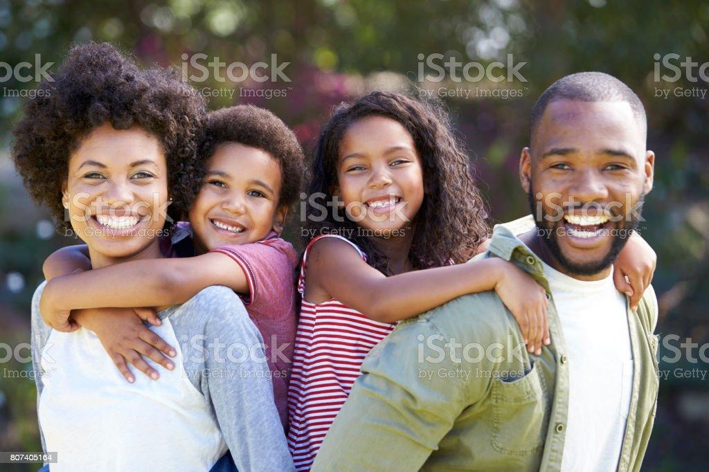 Portrait Of Parents Giving Children Piggybacks In Garden stock photo