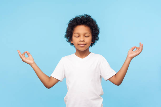 Portrait of peaceful cute little boy holding fingers in mudra gesture and meditating with closed eyes, feeling calm positive Portrait of peaceful cute little boy holding fingers in mudra gesture and meditating with closed eyes, feeling calm positive and relaxed, yoga practice. indoor studio shot isolated on blue background yogi stock pictures, royalty-free photos & images