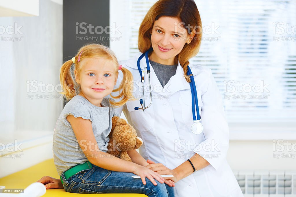 Portrait of pediatrician and little girl patient. stock photo