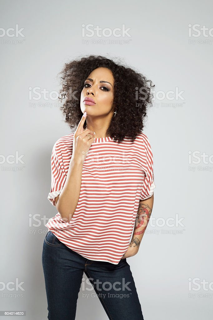 Portrait of pensive afro american young woman Portrait of pensive afro american young woman wearing casual striped top, standing against grey background with finger on chin, looking at camera. Adult Stock Photo