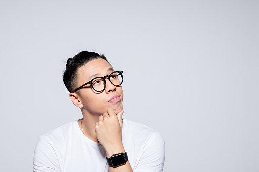 Headshot of worried asian young man wearing white t-shirt and glasses, looking at copy space with hand on chin. Studio portrait on white background.