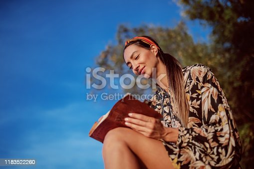 891402486 istock photo Portrait of pensive attractive caucasian brunette in floral dress and with headband sitting on rock on shore next to river and writing diary. 1183522260