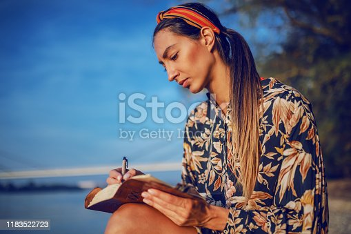891402486 istock photo Portrait of pensive attractive caucasian brunette in floral dress and with headband sitting on rock on shore next to river and writing diary. 1183522723