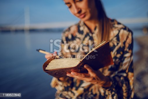 891402486 istock photo Portrait of pensive attractive caucasian brunette in floral dress and with headband sitting on rock on shore next to river and writing diary. 1183522840