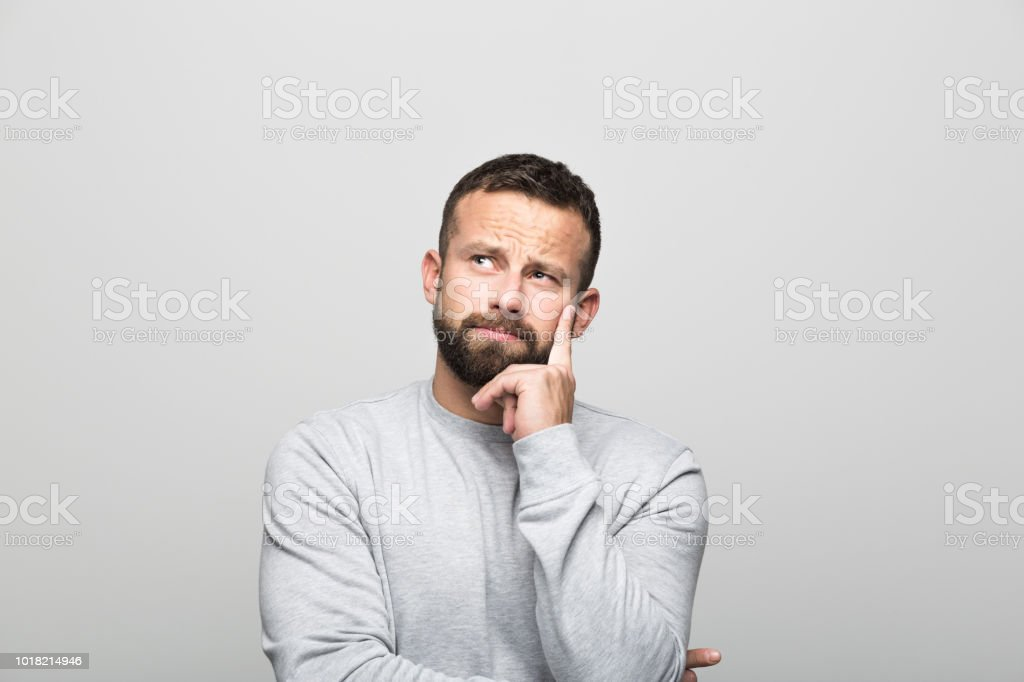 Portrait of pensive bearded young man, grey background Portrait of pensive bearded young man looking away with hand on chin. Studio shot, grey background. 30-34 Years Stock Photo