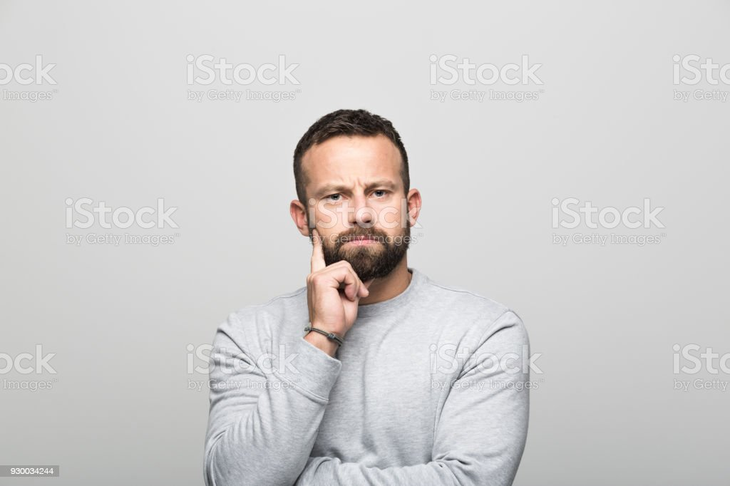 Portrait of pensive bearded young man, grey background Portrait of pensive bearded young man looking at camera with hand on chin. Studio shot, grey background. 30-34 Years Stock Photo