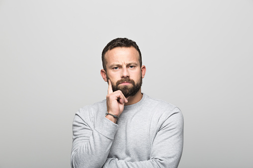 Portrait Of Pensive Bearded Young Man Grey Background Stock Photo - Download Image Now