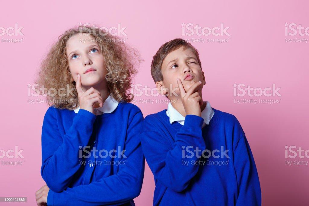 Portrait of pensive cute schoolboy and schoolgirl Pensive school children wearing school uniforms standing against pink background with hands on chins, looking up. Studio shot. 8-9 Years Stock Photo
