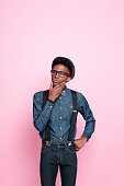 Studio portrait of pensive afro american young man wearing denim shirt and trausers, hat, nerd glasses and bowtie, thinking with hand on chin. Studio portrait, pink background.