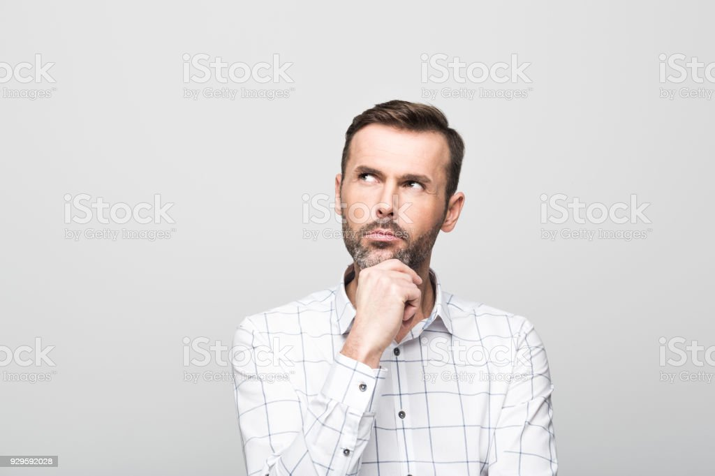 Portrait of pensive, handsome man, grey background Studio portrait of pensive, handsome businessman wearing white shirt, standing with hand on chin against grey background. 30-39 Years Stock Photo