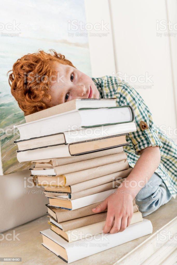 책 더미에 기대어 잠겨있는 작은 소년의 초상화 royalty-free 스톡 사진
