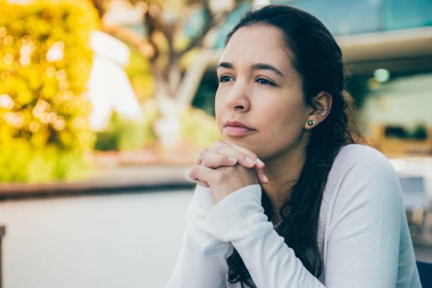 Porträt einer nachdenklichen oder traurigen jungen Frau, die im Straßencafé sitzt – Foto