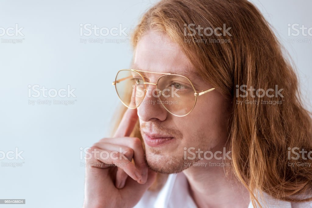 portrait of pensive stylish businessman with curly hair and glasses isolated on white zbiór zdjęć royalty-free