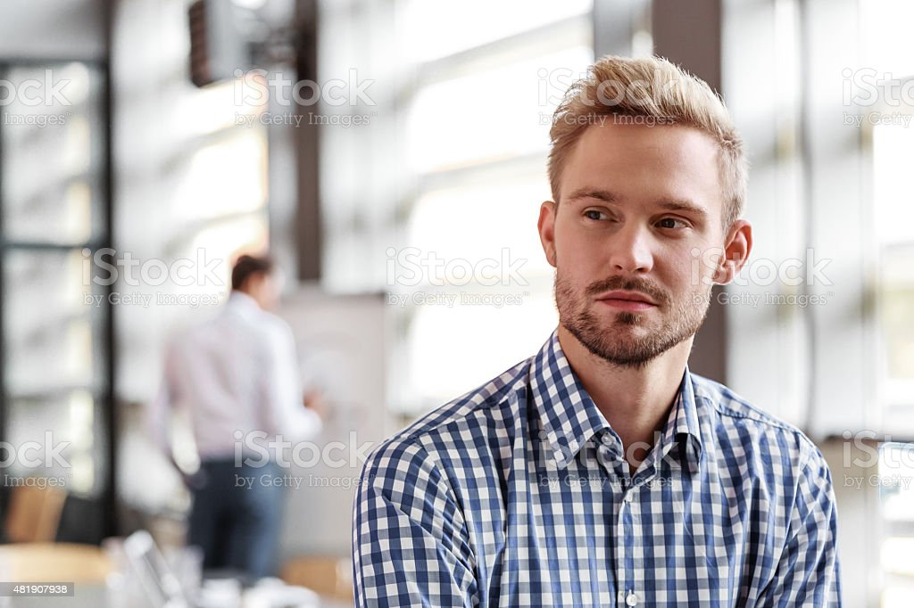 Portrait of pensive young businessman in the office Portrait of pensive young blond hair bearded businessman wearing checkered shirt sitting in the board room and looking away. Coworker in the background. 2015 Stock Photo
