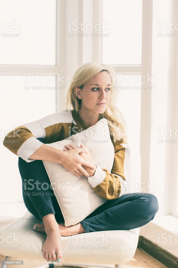 Portrait of pensive young woman sitting at home stock photo