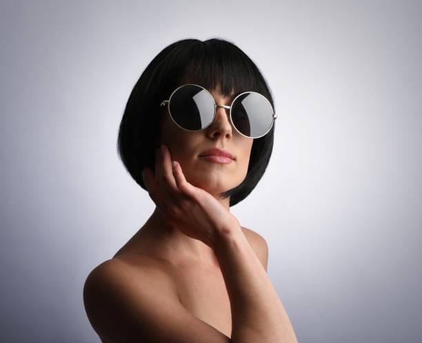 Porträt einer nachdenklichen jungen Frau, die eine Sonnenbrille trägt. – Foto